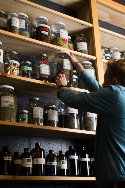 One of Railyard Apothecary's in Burlington, Vermont employees reaching for one of their many jarred herbs.