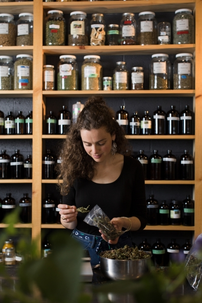 One of Railyard Apothecary's in Burlington, Vermont employees processing herbs for their stock.